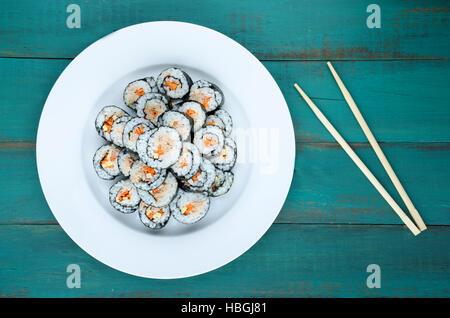 Gunkan Maki Sushi Roll placa o charola. Servido con palillos, sobre un fondo de madera en bar restaurante japonés. Vista superior, plano laical. Foo