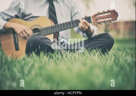 Joven tocando la guitarra en el césped Foto de stock