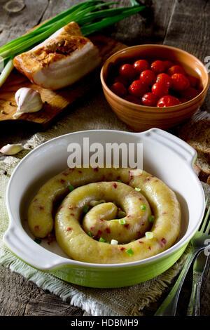 Salchicha horneados caseros con patatas y beicon en un fondo rústico.