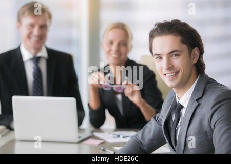 Grupo de gente de negocios y un sonriente joven