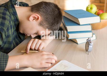 Cansado colegial dormido en un escritorio, mientras que hacer los deberes en casa