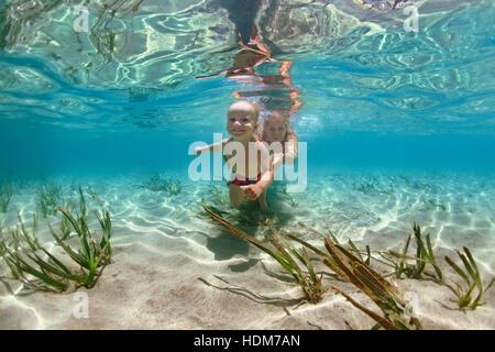 - Madre de familia feliz con el bebé nadar, bucear bajo el agua con la diversión en el mar, piscina. Matriz activa de la gente, el agua, el deporte de aventura al aire libre.