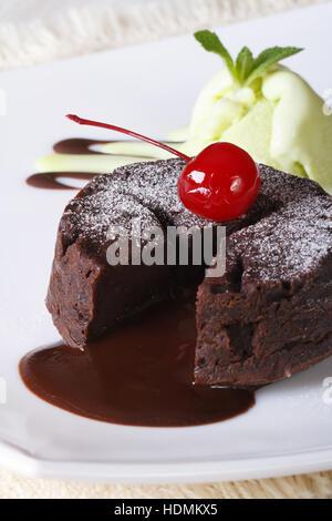 Fondant de chocolate con cerezas Pastel y helado de menta en una placa vertical de cerca.
