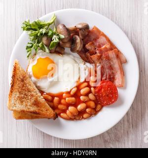 Desayuno inglés: huevo frito, bacon, tostadas y frijoles en una placa cercana vista desde arriba de la horizontal.