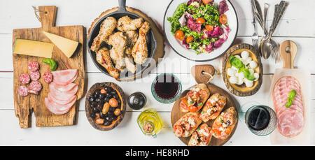 Tabla rústica con pollo, ensaladas, diferentes aperitivos y vino