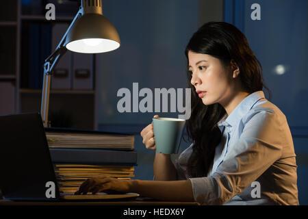 Mujer de negocios asiáticos beben café refrescante trabajando horas extraordinarias nocturnas interiores oficina de fondo.
