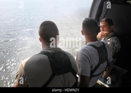 El capitán del ejército estadounidense Raymond Childress, derecha, 982nd Combat Camera Company (Airborne), East Point, Ga., conversa con otros soldados mientras está sentado dentro de un UH-60 Black Hawk durante la operación helocast entrenamiento en Tampa Bay, Florida, 27 de julio de 2013. Soldados con cámara de combate 982nd Company (Airborne) stand by en barcos para recuperar compañeros soldados fuera del agua. (Ee.Uu. Foto del ejército por el SPC. Tracy McKithern/liberado) operaciones Helocast 130727-A-LC197-769