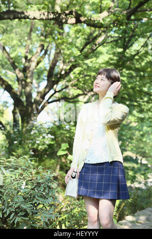 Jovencita japonesa en un parque de la ciudad
