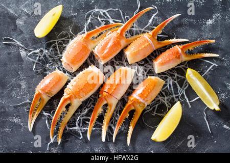 Pinzas de cangrejo con limón, sal y pimienta sobre un fondo de hormigón - Concepto de comida sana, dietas y cocina. Vista desde arriba.