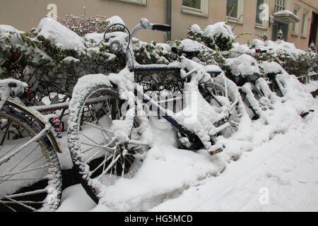 Bicicletas cubierto con nieve en invierno bloqueado en una valla junto al edificio y sendero