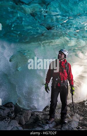Escalador de hielo en la cueva de hielo en Breidamerkurjokull Breiðamerkurjökull cueva de hielo, Cueva de cristal en el Parque Nacional de Vatnajökull, Sudeste de Islandia en enero
