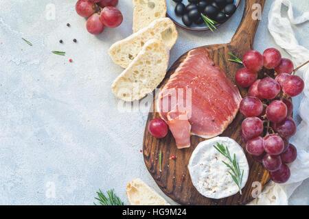 Charola con baguette fresco, carnes curadas, uvas, queso y aceitunas. Entremeses o tapas. Vista superior, espacio de copia