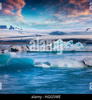 Flotación de icebergs azules en la Laguna glaciar Jokulsarlon. Colorido atardecer en el Parque Nacional Vatnajokull, el sureste de Islandia. Foto de stock