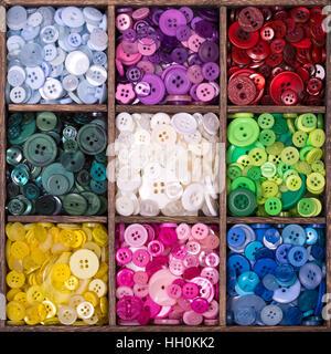 Caja de almacenamiento de madera cuadrada con 9 compartimentos, rellenos con una selección de coloridos botones agrupados por color.
