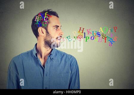 Vista lateral vertical hombre hablando con las letras del alfabeto en su cabeza y que sale de la boca abierta aislado sobre la pared gris de fondo. Expresiones de rostro humano