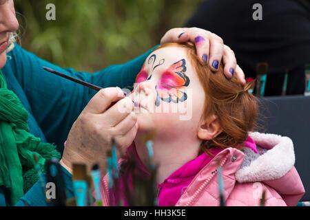 Niña joven con una mariposa pintada en su rostro en Glasshouse, RHS Garden Wisley, Woking, Surrey, Inglaterra, Reino Foto de stock