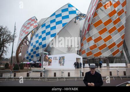 Cola de visitantes de la Fondation Louis Vuitton en el Bois de Boulogne en París, Francia. La gente espera por el control de seguridad para visitar la exposición de iconos del arte moderno de la colección Shchukin. La exposición durará hasta el 5 de marzo de 2017. El edificio diseñado por el arquitecto Frank Gehry fue terminado en 2014. Velas de colores son la instalación temporal titulado Observatorio de Luz (2016) por el artista francés Daniel Buren.
