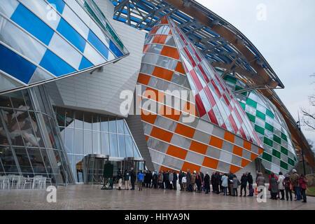 Cola de visitantes de la Fondation Louis Vuitton en el Bois de Boulogne en París, Francia. La gente espera por el control de seguridad para visitar la exposición de iconos del arte moderno de la colección Shchukin. La exposición durará hasta el 5 de marzo de 2017. El edificio diseñado por el arquitecto Frank Gehry fue terminado en 2014. Filtros de color en el cristal se navega la instalación temporal in situ titulado Observatorio de Luz (2016) por el artista francés Daniel Buren.