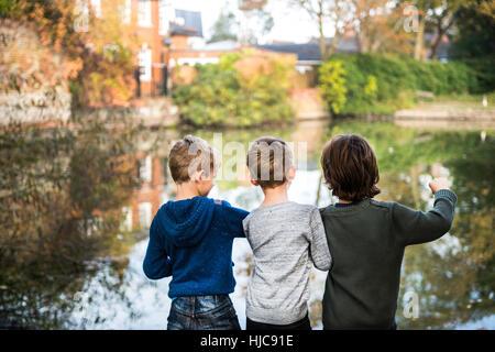 Tres jóvenes, de pie al lado del lago, vista trasera