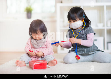 Dos hermanas japonés feliz jugando con los médicos establecidos en blanco capet en casa