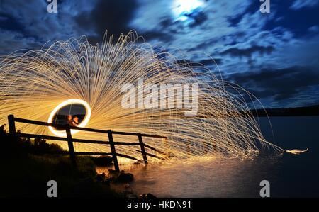 Una larga exposición de hilado de lana de acero en una con chispas se refleja en un lago