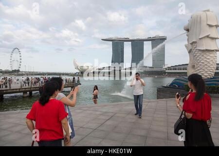 Singapur, Singapur - 22 de febrero de 2016: Los turistas toman fotos en frente de la Marina Sands Building y la estatua Merlion en la bahía de Singapur