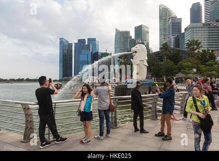 Singapur, Singapur - 22 de febrero de 2016: Los turistas toman fotos en frente de la ciudad famosos rascacielos y la estatua Merlion.