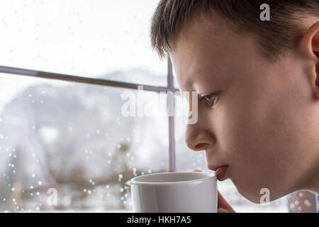 Pensativo Chico con taza de té en la mano mirando por la ventana en invierno con nieve Paisaje Forestal de la montaña