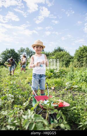 Pequeño niño sosteniendo switchblade con carretilla de jardín comunitario, Baviera, Alemania