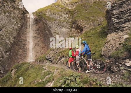 Tres ciclista de montaña amigos viendo la cascada, Zillertal, Tirol, Austria