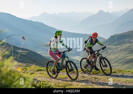 Dos ciclista de montaña amigos montando en subida, Zillertal, Tirol, Austria