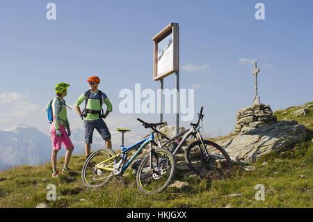 Pareja joven de mountainbikers viendo information board cuesta arriba, Zillertal, Tirol, Austria