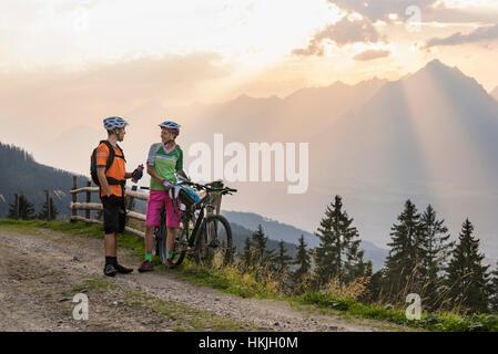 Pareja joven de ciclistas de montaña de pie en el camino de tierra durante la puesta de sol, Zillertal, Tirol, Austria