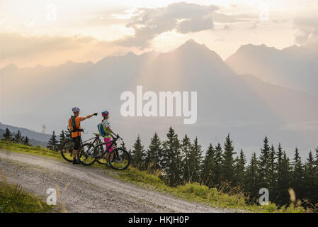 Pareja joven de ciclistas de montaña de pie en camino de tierra y mirando a ver durante la puesta de sol, Zillertal, Tirol, Austria