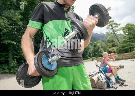 Joven levantando pesas mientras la mujer está en el fondo del agua potable, Kampenwand, Baviera, Alemania Foto de stock