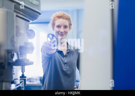 Joven ingeniero que sujetan el engranaje en una planta industrial, Friburgo de Brisgovia, Baden-Wurtemberg, Alemania