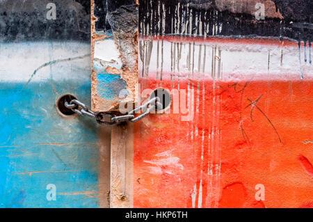 Cadena con candado en una antigua puerta de madera pintada de dos colores, azul y rojo