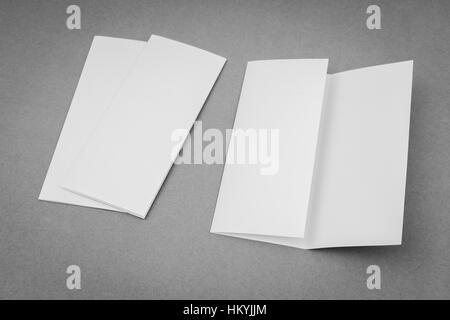 Plantilla en blanco de papel doblado en tríptico sobre fondo gris