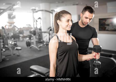 Adulto joven mujer trabajando en el gimnasio, haciendo flexiones de brazos (bíceps) con la ayuda de su entrenador personal.