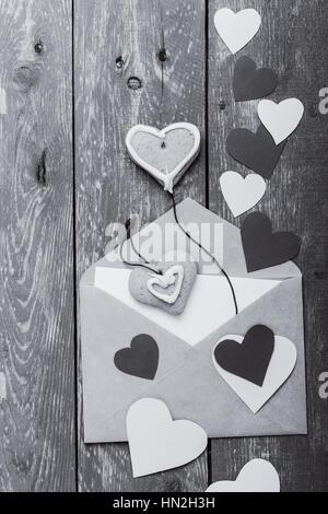 Sobres con corazones de papel artesanal y cookies en forma de corazón azul de madera rústica mesa. Día de San Valentín tarjeta de felicitación en blanco y negro con sepia, efecto