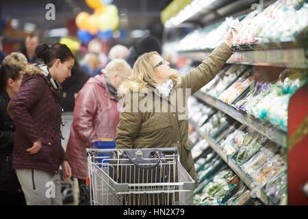 Interior ocupado de compradores con recogida de tranvía desde la estantería en la isla vegetal de descuento en compras Foto de stock