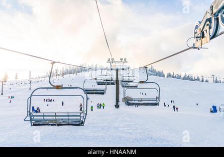 Hermoso ski lift sobre la nieve en la estación de esquí de montaña con el cielo azul de fondo.