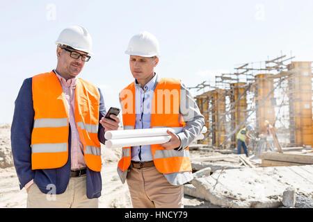 Ingenieros a través de teléfono móvil en el sitio de construcción contra el cielo claro Foto de stock