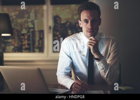 Retrato de graves al empresario positivo oficina, mirando a la cámara