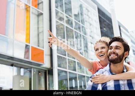 Mujer alegre mostrando algo al hombre mientras disfruta piggyback paseo en ciudad