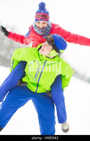 Feliz viaje piggyback joven dando a la mujer en la nieve