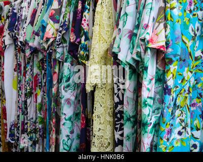 Grupo de coloridos vestidos de mujer a la venta en un mercado en un rack