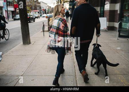 Pareja joven paseando a un perro a lo largo de calle, vista trasera