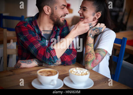 Pareja en la cafetería cara a cara sonriente