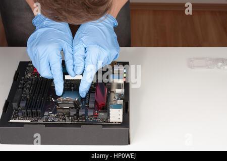 Joven con guantes tapón en la CPU en la motherboard socket LGA 1151